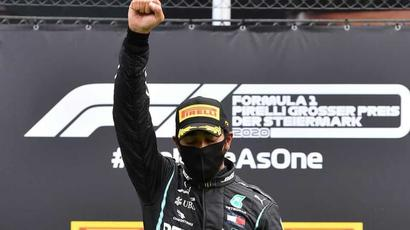 Lewis Hamilton raises a fist after his first win of the season